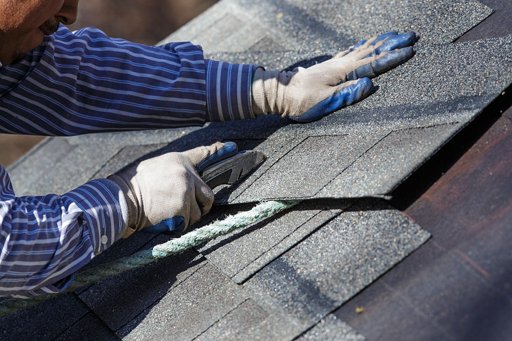 A man installing the roof