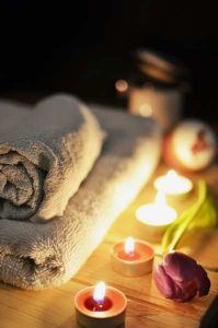 A relaxing setting with towels and candles that can be used to relax when finding an affordable apartment in Red Hook