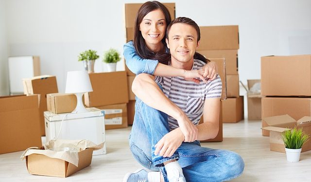 A couple hugging, moving boxes behind them