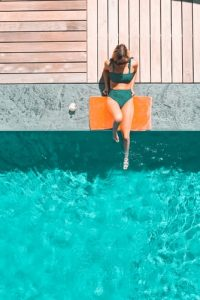 A young woman chilling and tanning on the side of a pool.