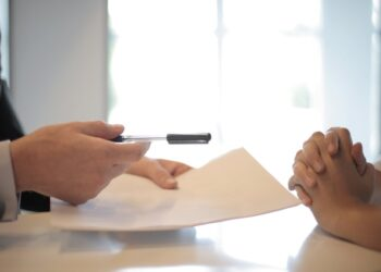Two men consider moving insurance in a meeting.